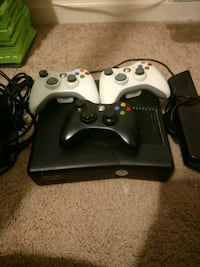 black Xbox 360 console with three controllers
