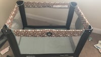 black and beige travel cot 23 mi