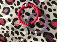 three pink, purple, and clear lokai bracelets