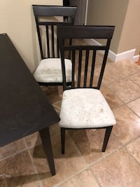 Wooden dining table with 4 white padded chairs