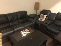 Two Black reclining leather couches, one dark wood coffee table with two footstools, two dark wood end tables. New York, 11221