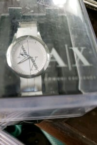 round silver analog watch with white leather strap