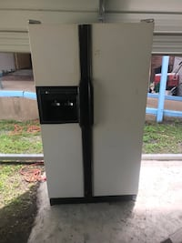white and black side-by-side refrigerator with dispenser