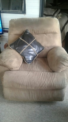 brown suede recliner chair and brown throw pillow