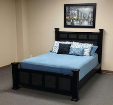 black wooden bed with blue and white comforter set