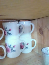 four white-and-pink floral ceramic mugs