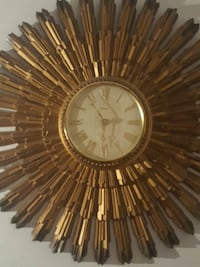 round gold-colored burst analog wall clock