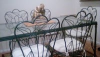 Wrought iron and glass table.  Dark green in color.  Fashioned leaves adorn the backs of six chairs.  Pristine condition! Frederick