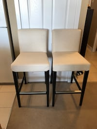 two white padded brown wooden chairs Toronto, M9A