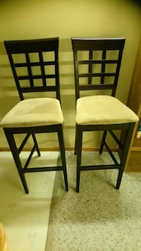 two brown wooden framed white padded chairs