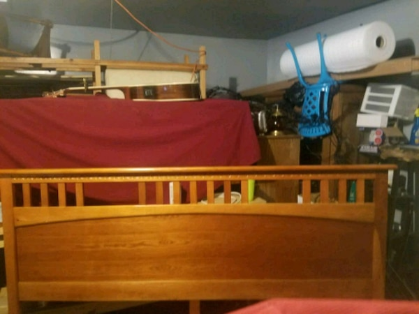 brown wooden bed frame with red bed sheet