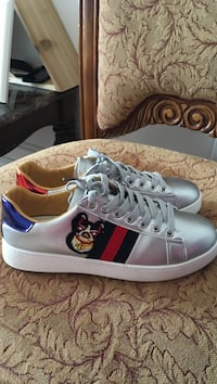 pair of gray Gucci sneakers