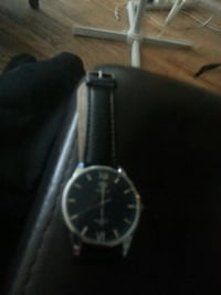 round silver analog watch with black leather strap Surrey