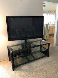 Black flat screen tv; brown wooden tv stand Mission Viejo, 92692