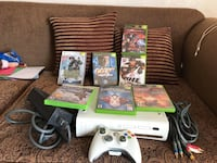 white Xbox 360 console with controllers and game cases