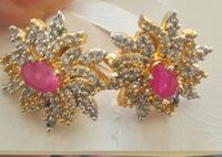 pair of gold-colored with pink stone studded earrings