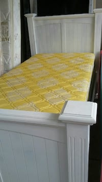 yellow and white mattress on white wooden bed frame