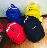 four red, black, blue, and yellow Supreme backpack