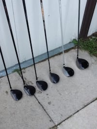 four black and gray golf clubs