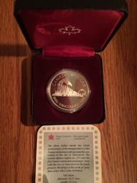 silver-colored Canadian dollar coin with red box Barrie, L4N 4G4