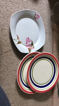 rectangular white floral ceramic plate; two round white-green-and-red ceramic plates