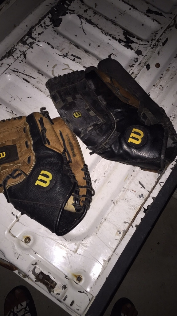 two black Wilson leather baseball mitts