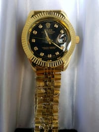round gold-colored Rolex analog watch with link band 536 km