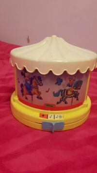 white, yellow, and pink Disney Mickey Mouse and Donald Duck printed musical carousel toy