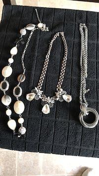 three assorted silver-colored chain necklaces