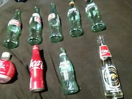 9 empty Coca Cola bottles