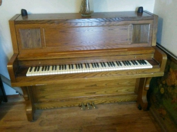 brown wooden upright piano with chair 86ee4fd2-f404-4bce-acac-2051d0d310d0