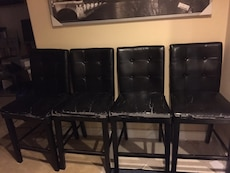 four tufted black leather bar stools