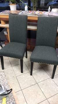 Two gray padded chairs with brown wooden frames 24 km