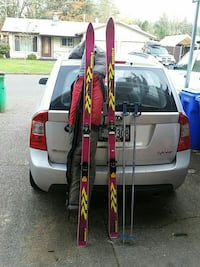 pair of pink-and-yellow snow skis and sticks