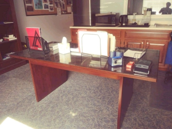 brown wooden desk with glass top