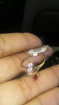 gold-colored diamond and red gemstone ring