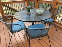 round black metal patio table with four chairs Oakton