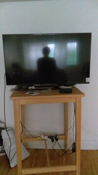 black flat screen TV with brown wooden TV stand Montréal, H3W 1W7