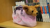 brown dog plush toy with pink pet carrier bagh