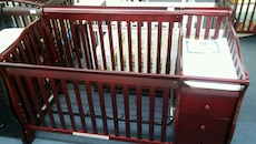 red wooden crib with drawers