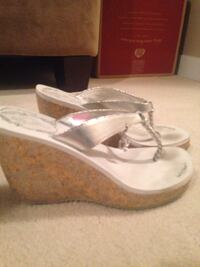 Pair of silver white wedge sandals by Baby Phat Delta