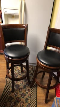 two black leather padded brown wooden chairs