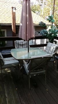 Table and 4 chairs. Includes 9 ft solar umbrella   277 mi