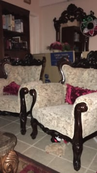two brown wooden framed white padded armchairs