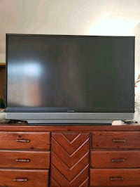 """65""""black flat screen TV with brown wooden TV stand Santa Ana, 92703"""