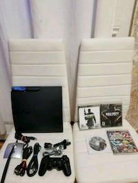 black Sony PS3 Slim with controllers and game cases Dollard-des-Ormeaux, H9B 1Z6