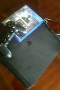 black Sony PS4 console with controller and game cases Los Angeles County