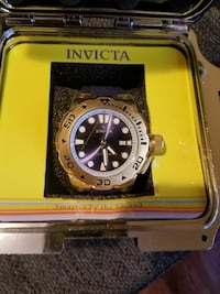 round silver Invicta analog watch with black leather strap
