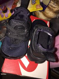 toddler's pair of black Nike shoes