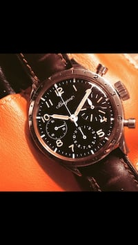 Round black chronograph watch with black leather strap